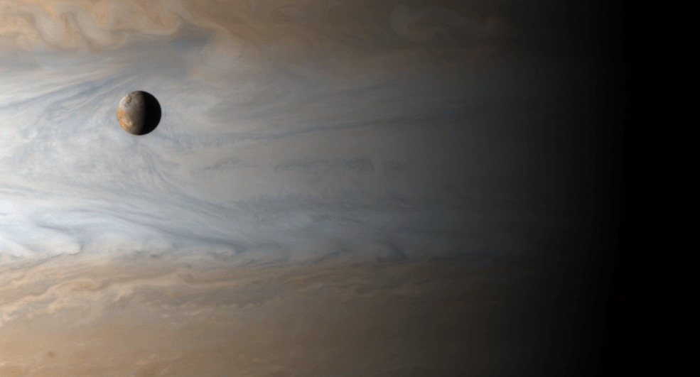 The moon Io orbits Jupiter in this image from NASA's Cassini spacecraft. Jupiter and Io appear deceptively close in this image, when in fact the moon is orbiting 217,000 miles from the gas giant planet. (Image: NASA/JPL/University of Arizona)