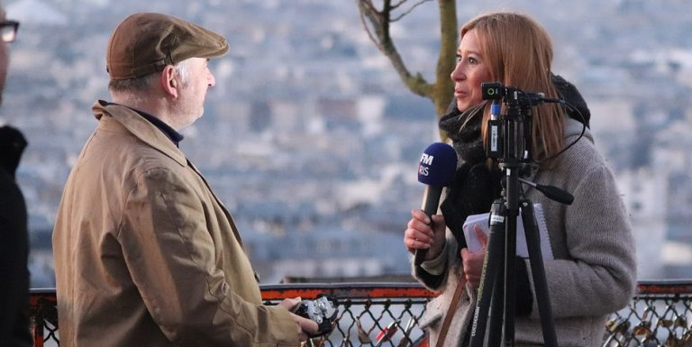 A female journalist does an outdoor interview of a man in a tan hat and coat.