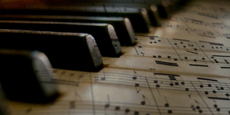 Black piano keys with a sheet of music overlaid.