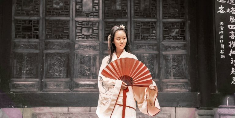 A Chinese girl wearing traditional clothing and carrying a fan.