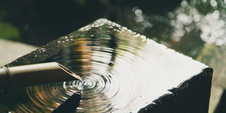 A bamboo spout with water pouring out.