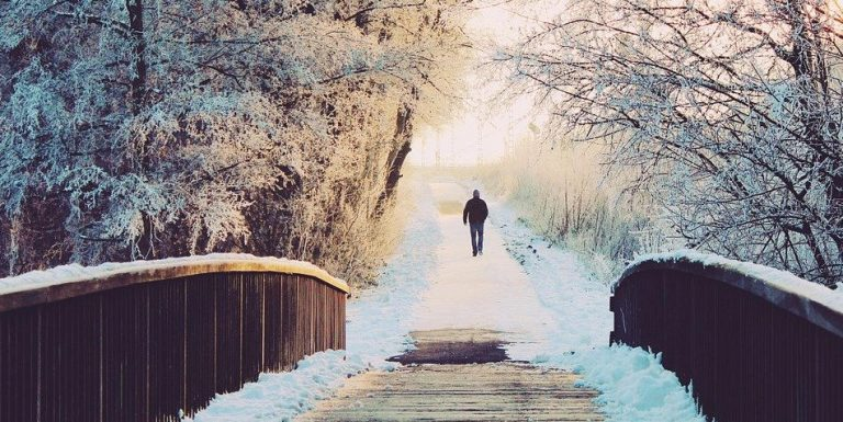 A man walking along a snow covered trail.