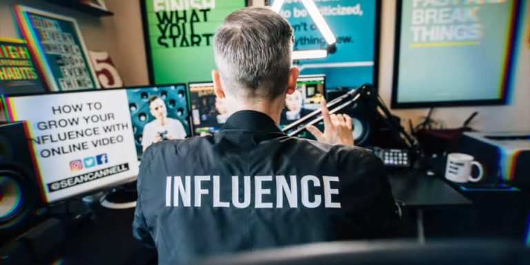 """Man sitting in front of a microphone and computer wearing a shirt that says """"Influence"""""""