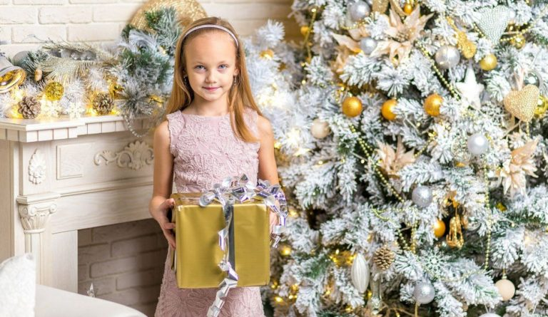 A girl with a gift stands next to a Christmas tree.