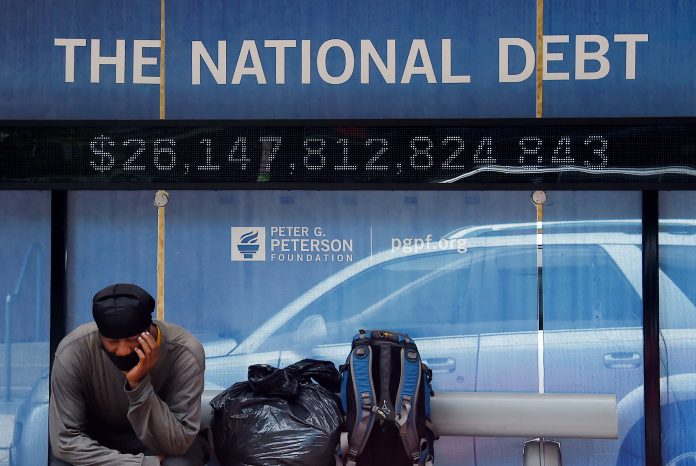 A man waits at a bus stop that displays the national debt of the United States on June 19, 2020 in Washington, DC. Senate Democrats pushed through the controversial $1.9 trillion American Rescue Plan Act of 2021 by a 50 - 49 partisan vote.