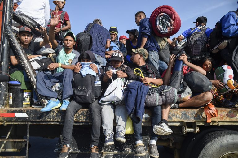 Central American migrants -mostly honduran- taking part in a caravan to the US, get on board a truck heading to Irapuato in the state of Guanajuato on November 11, 2018 after spending the night in Queretaro in central Mexico. - The United States embarked Friday on a policy of automatically rejecting asylum claims of people who cross the Mexican border illegally in a bid to deter Central American migrants and force Mexico to handle them.