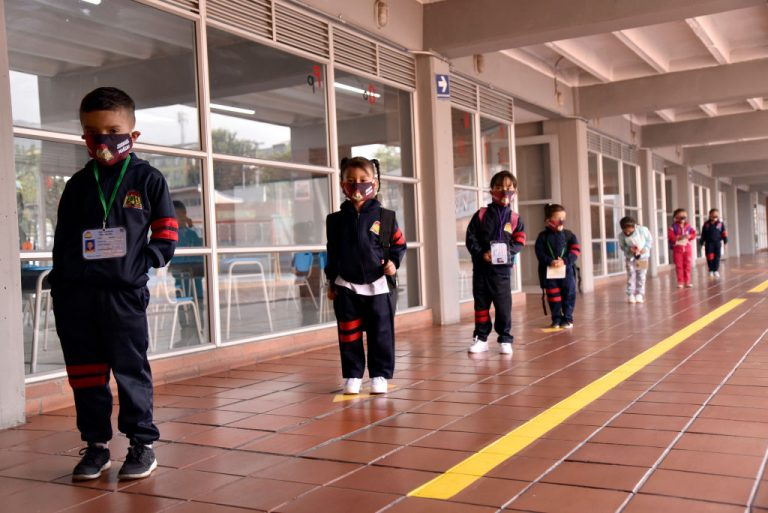Preschool students wear face masks and obey social distance to comply with measures as instructed as they line up to begin the first day back to in-person class at Enrique Olaya Herrera public school on February 16, 2021 in Bogota, Colombia