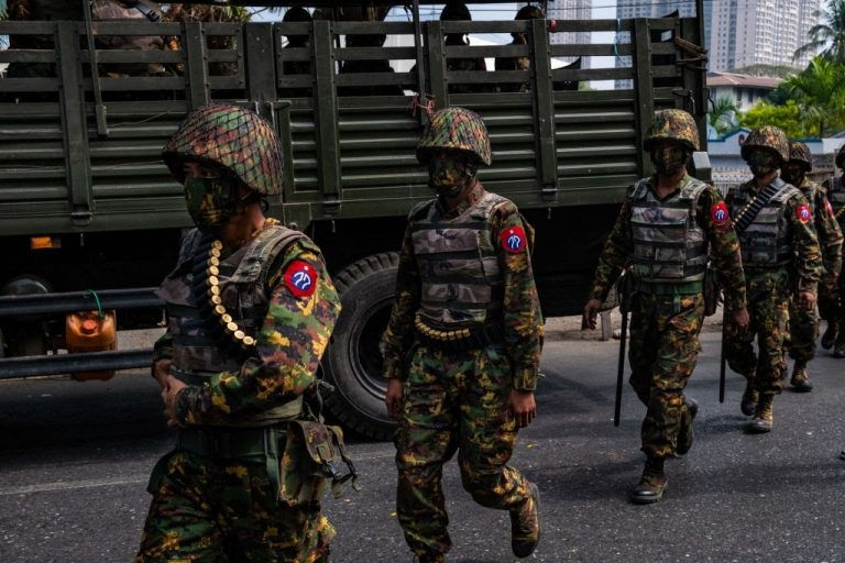Myanmar (Burma) military soldiers stand guard after arriving overnight with armoured vehicles on February 15, 2021 near the Central Bank in Yangon, Myanmar.