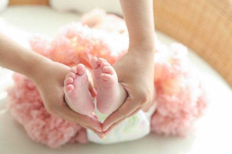 A woman holding a baby girl's feet.