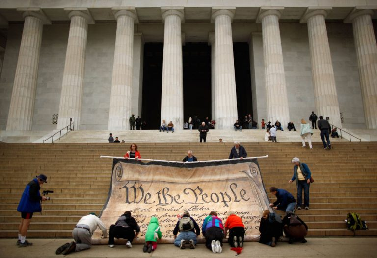 Volunteers help roll up a giant banner printed with the Preamble to the United States Constitution during a demonstration against the Supreme Court's Citizens United ruling at the Lincoln Memorial on the National Mall October 20, 2010 in Washington, DC