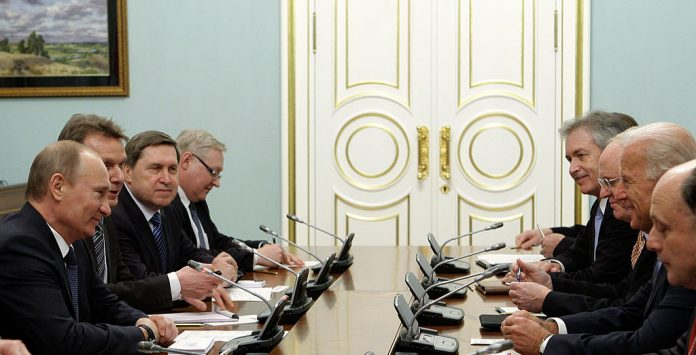 Russian Prime Minister Vladimir Putin (L) and then-U.S. Vice President Joe Biden (2nd R) meet on March 10, 2011 with their delegations in Moscow. Tensions between Moscow, Washington, Putin, and Biden trace directly back to a U.S. Intelligence Community report claiming Russia was the primary actor in 2020 federal election interference, while communist China was merely a bystander
