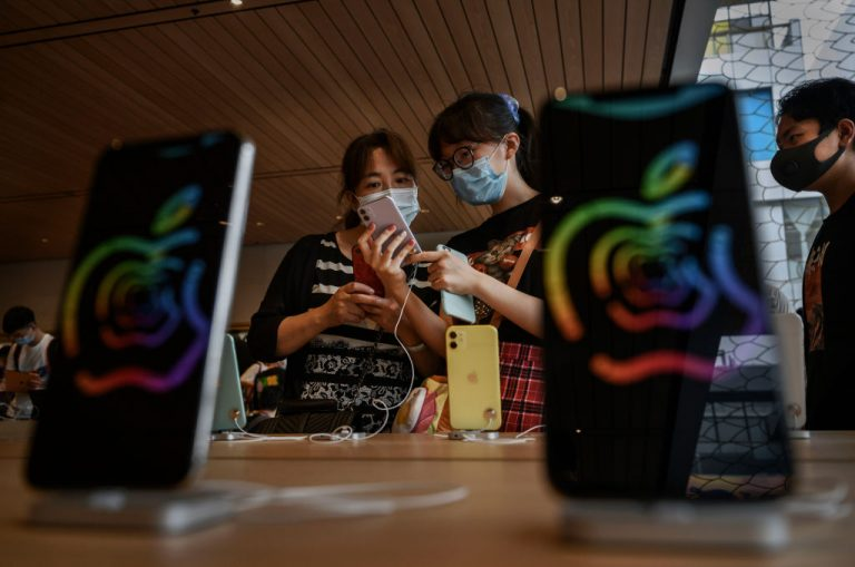 Chinese customers look at iphones at the official opening of the new Apple Store in the Sanlitun shopping area on July 17, 2020 in Beijing, China. As Apple rolls out new privacy measures in iOS 14, Chinese state-backed China Advertising Association is working with Tencent and ByteDance to circumvent the measures