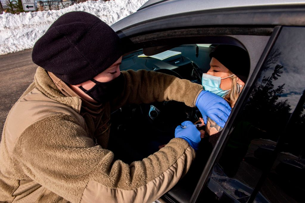 A soldier vaccinates a woman in her car at a vaccination center in Londonderry, New Hampshire on February 4, 2021. Concerning data of COVID-19 vaccine miscarriages and stillbirths are present in the CDC's Vaccine Adverse Event Reporting System (VAERS).