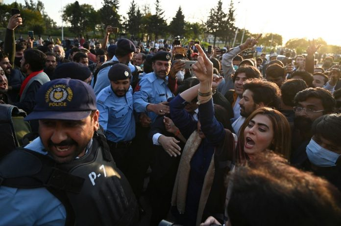 Policemen stand in the middle as activists (L) of the ruling party Pakistan Tehreek Insaf (PTI) and supporters (R) of opposition coalition of the Pakistan Democratic Movement (PDM) party confront during the Pakistan Senate election, outside the Senate building in Islamabad on March 12, 2021.