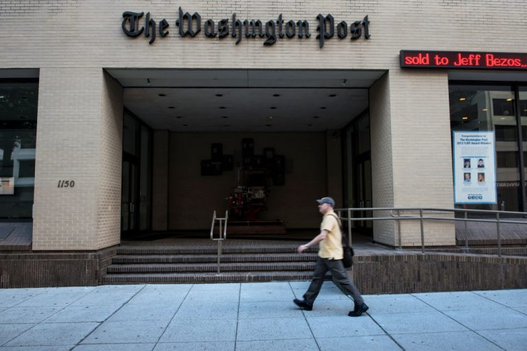 A man walks past The Washington Post building on August 5, 2013 in Washington, D.C., after it was announced that Amazon founder and CEO Jeff Bezos had agreed to purchase the Post for USD 250 million. The Washington Post correction of a January story about Donald Trump's call to a Georgia official reveals gaps in big media's integrity standards.