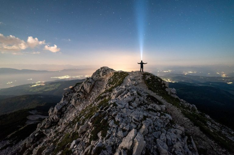 A man stands on top of a mountain and a beam of light appears to shoot out from his head up into the heavens.