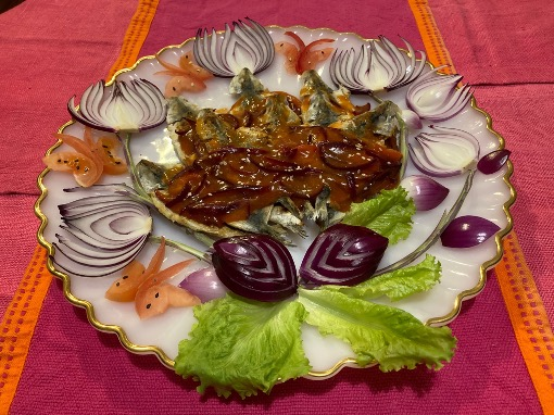 A plate of sardines in tomato sauce garnished with vegetables cut into fancy shapes.