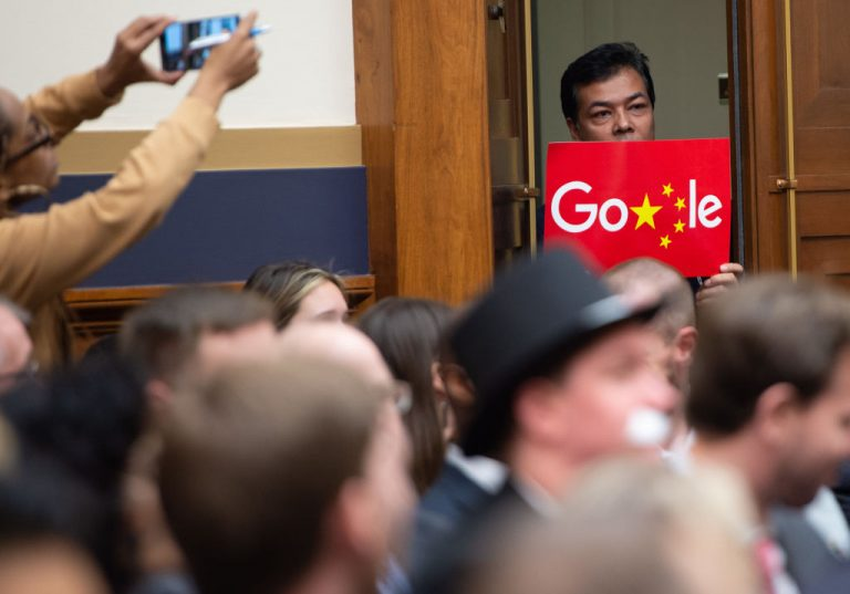 """A demonstrator holds a sign in protest as Google CEO Sundar Pichai testifies during a House Judiciary Committee hearing on Capitol Hill in Washington, DC, December 11, 2018. Google chief executive Sundar Pichai was grilled by US lawmakers over allegations of """"political bias"""" by the internet giant, concerns over data security, and its domination of internet search."""