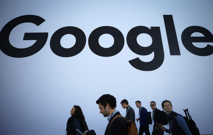 People walk past the Google pavilion at CES 2020 at the Las Vegas Convention Center on January 8, 2020 in Las Vegas, Nevada.