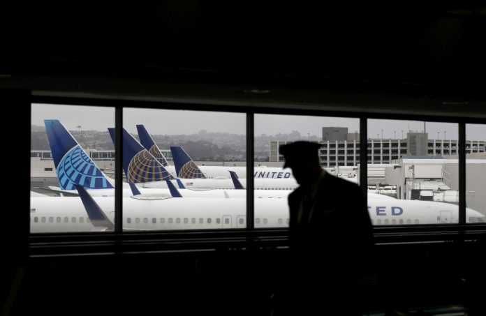 A pilot walks by United Airlines gated planes at San Francisco International Airport. United Airlines seeks to shift this male dominated field, announcing that 50 percent of new pilots will be women or people of color.