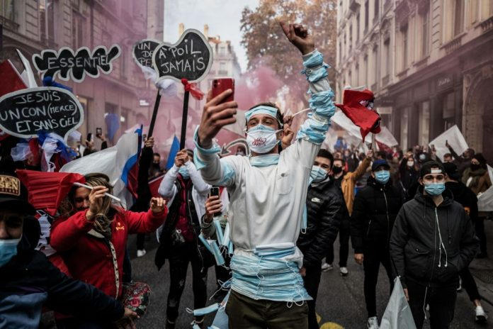 TOPSHOT - A man gestures and takes a selfie during a protest against the restrictions imposed by the government as part of lockdown measures in Lyon on November 23, 2020. - Shop owners, restaurants owners and night clubs owners protest to call for the reopening of their stores closed as activity has ceased in their sector over coronavirus restrictions, during a national lockdown in France aimed at curbing the spread of the Covid-19 pandemic caused by the novel coronavirus.