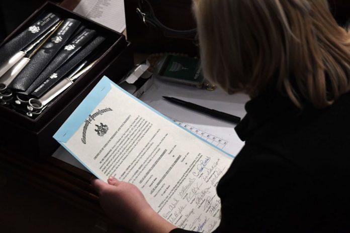 Una persona con il certificato di voto del Commonwealth della Pennsylvania durante la sessione congiunta del Congresso, mentre la sessione è stata ripresa in seguito alle proteste il del 7 gennaio al Campidoglio degli Stati Uniti a Washington DC.  (Immagine: SAUL LOEB / AFP tramite Getty Images)