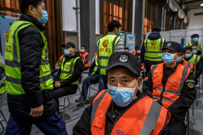 Chinese workers, including security guards, wait to receive a COVID-19 injection at a mass vaccination center for Chaoyang District on January 15, 2021 in Beijing, China. The CCP's vaccines are living up to the notoriously poor quality standards the world has come to expect from made-in-China products.