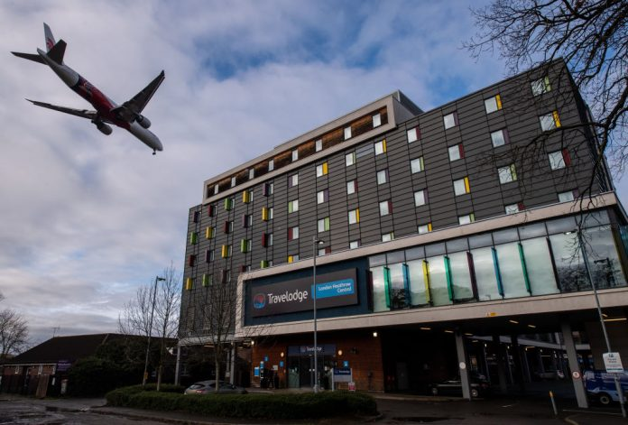 An airplane flies over a Travelodge Hotel as it comes in to land at Heathrow Airport on January 28, 2021 in London, England. New measures enacted by Prime Minister Boris Johnson's government will leave citizens with heavy fines if they leave the country for reasons outside certain, limited exemptions.