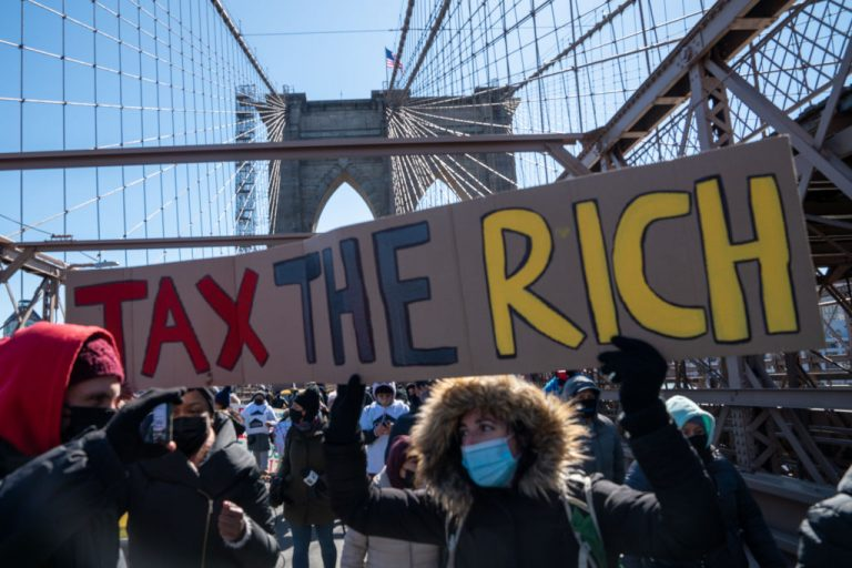 """Leftist demonstrators march across the Brooklyn Bridge holding a sign to """"tax the rich"""" to demand funding for excluded workers in the New York State budget on March 5, 2021 in New York City. Governor Cuomo and NY State Legislators approved a $212 billion budget that would increase taxes on the wealthy and corporations while providing a stimulus payout to undocumented workers more than 10 times higher than Federal stimulus checks."""
