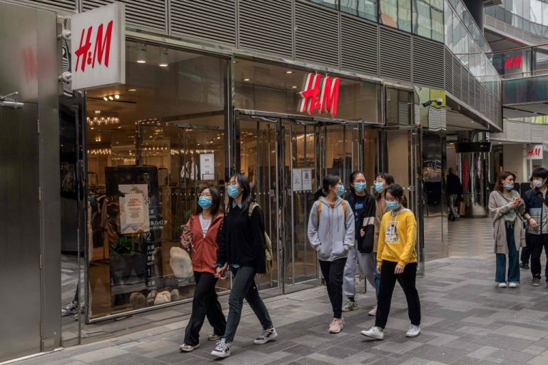 People walk past an H&M store in Beijing on April 5, 2021. A Xinjiang cotton boycott has led China's communist state to blur the brands involved on television.
