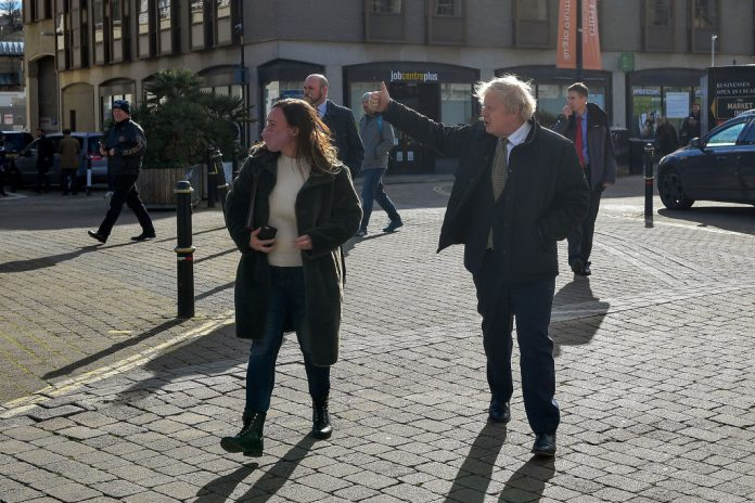 TRURO, ENGLAND - APRIL 07: British Prime Minister Boris Johnson (R) gives a thumbs-up to passers by as he walks to visit Ann's Cottage Surf Shop on April 7, 2021 in Truro, England. The Prime Minister visited businesses in Cornwall to see how they are preparing to reopen after the Coronavirus lockdown ahead of Step 2 of the roadmap on Monday 12 April.