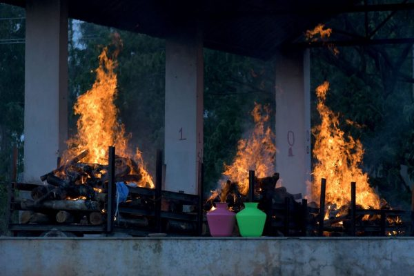 """Burning pyres of victims who lost their lives due to SARS-CoV-2/COVID-19 are seen at an open crematorium in Bangalore on April 26, 2021. India's pandemic statistics have surged exponentially. However, officials say there is not yet enough data to confirm if the wave is caused by the new """"Indian Variant."""""""