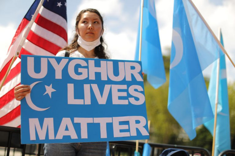 """Supporters and members of the East Turkistan National Awakening Movement rally outside the White House to urge the United States to end trade deals with China and take action to stop the oppression of the Uyghur and other Turkic peoples August 14, 2020 in Washington, DC. A Canadian couple who lived in Xinjiang for more than a decade described the conditions as a """"huge penitentiary."""""""