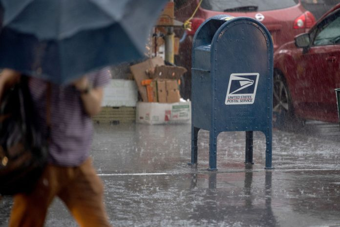 A person carrying an umbrella walks past a USPS mail box in the rain on August 25, 2020 in New York City. A team of the Postal Service's law enforcement arm specializing in covert internet operations has been found surveilling social media and communication platforms such as Telegram and Parler for right-wing content.