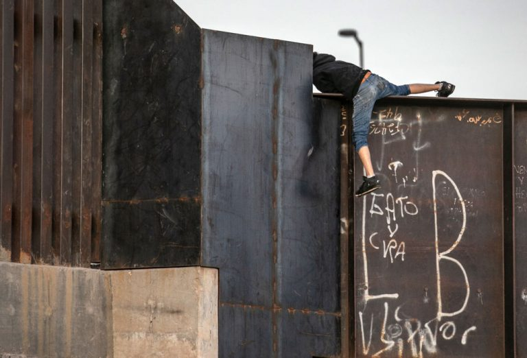 An immigrant, who said he was a 16-year old from Mexico, climbs over the border wall after crossing the Rio Grande into the United States on March 15, 2021 in Ciudad Juarez, Mexico. Joe Biden has said he does not plan to resume construction of Trump's border wall after a leaked presentation by DHS Secretary Alejandro Mayorkas to Immigrations and Customs Enforcement appeared to show otherwise.