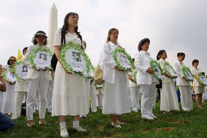 At a rally in Washington, DC July 19, 2001, Falun Gong practitioners hold photos of fellow members who died at the hands of the Chinese Communist Party, marking the second anniversary of Jiang Zemin's persecution of Falun Gong, the largest spiritual group in China facing severe persecution.