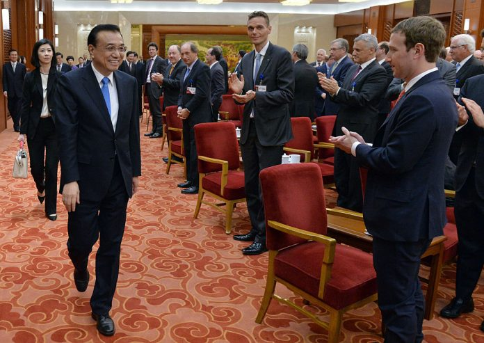 Facebook CEO Mark Zuckerberg (R) and the overseas representatives of the China Development Forum applaud as Chinese Premier Li Keqiang arrives for a meeting in Beijing on March 21, 2016. 'Zuck' has been selling his company's influence on the world's people to the Chinese Communist Party so it can whitewash and astroturf about the genocide of Uyghur Muslims in the Xinjiang Autonomous Zone.