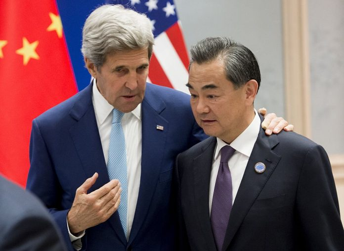 Former U.S. Secretary of State John Kerry speaks with Chinese Foreign Minister Wang Yi prior to the U.S. and China formally joining the Paris Climate deal at the West Lake State House in Hangzhou on September 3, 2016. The Biden administration has joined the Chinese Communist Party once again in making promises of changing the world in the name of climate change.