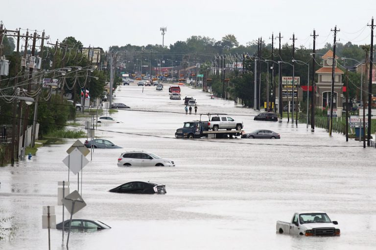 A car gets towed while men walk in the flooded waters of Telephone Rd. in Houston, Texas on August 30, 2017 after Hurricane Harvey. FEMA and the NFIP are bumping flood insurance rates for the first time in 50 years as a result of potential climate catastrophe, which may lead to enormous increases for homeowners in the highest risk areas.
