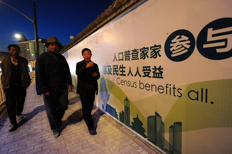 Pedestrians walk past a billboard for China's coming census on October 29, 2010 in Beijing. The release of data from China's 2020 Census has been repeatedly delayed. Many analysts speculate the communist nation is facing a severe population decline stemming from a multitude of hard-to-resolve factors.