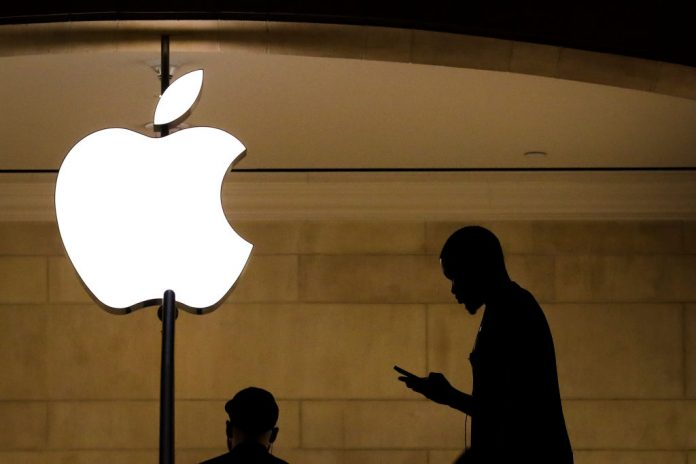 A man checks his phone in an Apple retail store in Grand Central Terminal, January 29, 2019 in New York City. Apple is breaching EU antitrust laws by charging an effective 30 percent tax on Apple Music competitor Spotify's positioning in its walled garden ecosystem App Store, says the European Commission