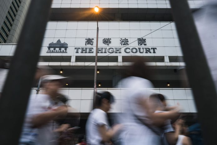 Hong Kong residents walk past the High Court in Admiralty during a protest against the government's controversial extradition law on June 9, 2019 in Hong Kong. The first person charged under the draconian, Beijing-installed National Security Law will be denied trial by jury.