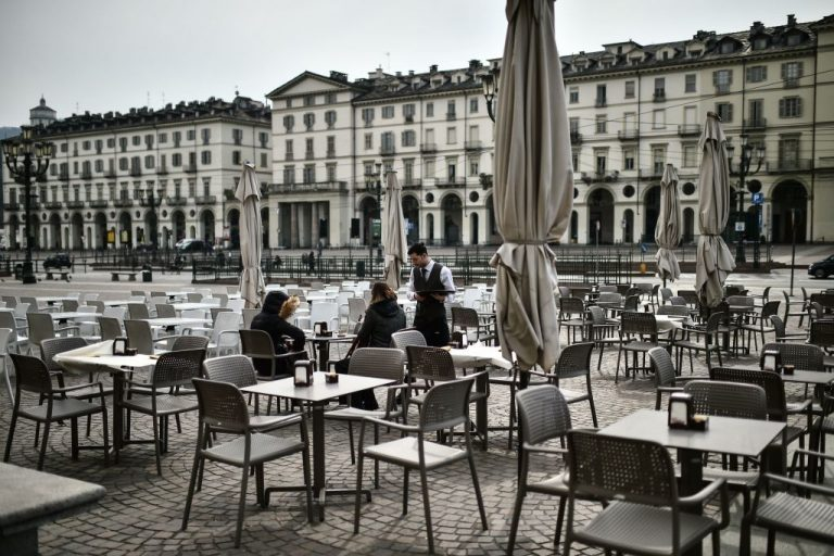 Customers order drinks at a deserted cafe terrace on March 9, 2020 on Piazza Vittorio in Turin, Italy. A Canadian researcher has found lockdowns have done 282 times more harm than lives they have purportedly saved.