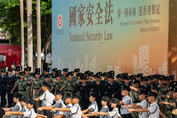 """Hong Kong Police put on a display of force at Golden Bauhinia Square in front of a propaganda banner promoting the NSL on July 1, 2020 in Hong Kong. The National Security Law has effectively eliminated democracy and installed totalitarianism years ahead of the expiration of the CCP's """"One Country, Two Systems"""" contract with England."""