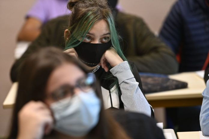 """A girl wearing a mask sits in a classroom in Brequigny high school in Rennes, western France, on September 1, 2020. France's Minister of National Education kiboshed the use of """"woke"""" inclusive wording and the use of the French """"midpoint"""" mechanic, fearing the language and its international reputation will otherwise be ruined."""
