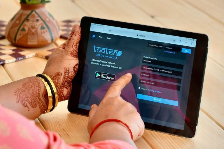 A woman browses through the login page of 'Tooter', a social network modelled after Twitter on a handheld tablet device, in Bangalore on November 30, 2020. Twitter has been defiant in response to India's new social media law.