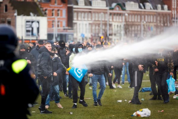 Demonstrators are sprayed by a police water cannon at Amsterdam's Museumplein during a protest against lockdowns on January 21, 2021.