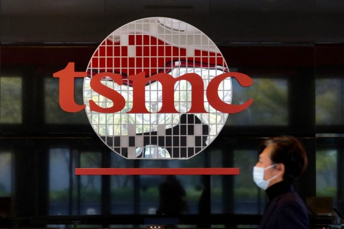 A man walks past a company logo at the headquarters of the world's largest semiconductor maker TSMC in Hsinchu on January 29, 2021. Sources say the world's largest chip manufacturer will expand to build five more plants in Arizona in the next three years.