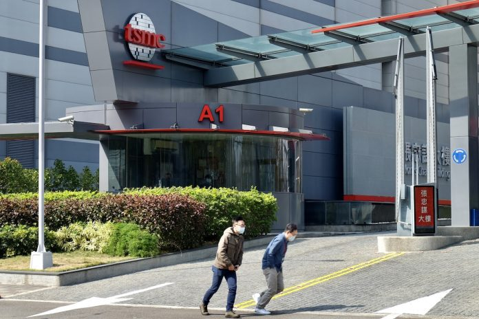 People walk past the headquarters of the world's largest semiconductor maker TSMC in Hsinchu on January 29, 2021.