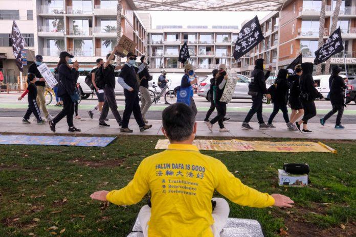 Un praticante del Falun Gong medita mentre i cittadini di Hong Kong passano davanti durante una marcia flash mob. Mostrano solidarietà ai 47 attivisti pro-democrazia di Hong Kong che sono stati accusati di sovversione contro il governo della città controllato dal Partito Comunista Cinese dopo aver organizzato e preso parte alle elezioni primarie, a Santa Monica, California, il 7 marzo 2021. (Immagine: RINGO CHIU / AFP tramite Getty Images)